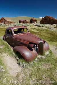Old car lying in dirt field, Fuller Street and Green Street buildings in background. Bodie State Historical Park, California, USA, natural history stock photograph, photo id 23162