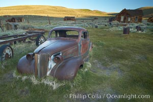 Old car lying in dirt field, Fuller Street and Green Street buildings in background. Bodie State Historical Park, California, USA, natural history stock photograph, photo id 23164