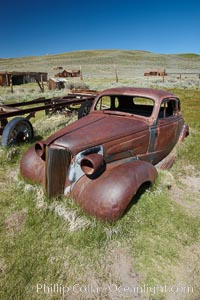 Old car lying in dirt field, Fuller Street and Green Street buildings in background, Bodie State Historical Park, California