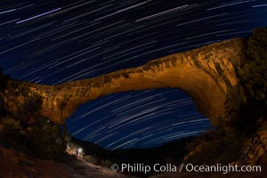 Owachomo Bridge and Star Trails, at night.  Owachomo Bridge, a natural stone bridge standing 106' high and spanning 130' wide,stretches across a canyon with the Milky Way crossing the night sky, Natural Bridges National Monument, Utah