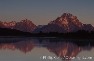Mount Moran in the Teton Range is reflected at sunrise in a sidewater of the Snake River at Oxbow Bend, summer, Grand Teton National Park, Wyoming