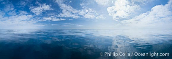 Ocean surface panorama, glassy calm ocean water offshore of California, clouds and sky