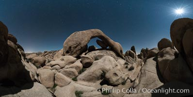 Panoramic image of Arch Rock lit by a full moon, Joshua Tree National Park, California