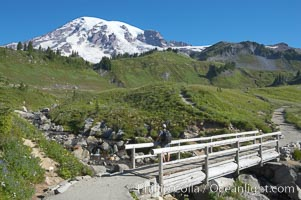 A hiker admires Mount Rainier from the footbridge crossing Edith Creek, Paradise Meadows, Mount Rainier National Park, Washington