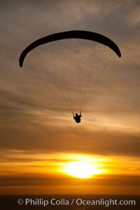 Paraglider soaring at Torrey Pines Gliderport, sunset, flying over the Pacific Ocean, La Jolla, California
