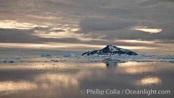 Paulet Island, near the Antarctic Peninsula, is a cinder cone flanks by lava flows on which thousands of Adelie Penguins nest