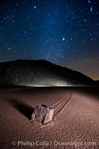 Racetrack sailing stone and Milky Way, at night. A sliding rock of the Racetrack Playa. The sliding rocks, or sailing stones, move across the mud flats of the Racetrack Playa, leaving trails behind in the mud. The explanation for their movement is not known with certainty, but many believe wind pushes the rocks over wet and perhaps icy mud in winter. Racetrack Playa, Death Valley National Park, California, USA, natural history stock photograph, photo id 27640