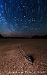 Racetrack sailing stone and star trails.  A sliding rock of the Racetrack Playa. The sliding rocks, or sailing stones, move across the mud flats of the Racetrack Playa, leaving trails behind in the mud. The explanation for their movement is not known with certainty, but many believe wind pushes the rocks over wet and perhaps icy mud in winter. Death Valley National Park, California, USA, natural history stock photograph, photo id 27667