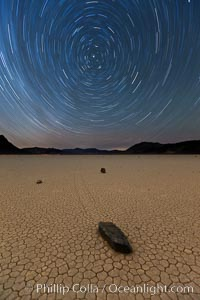 Racetrack sailing stone and star trails.  A sliding rock of the Racetrack Playa. The sliding rocks, or sailing stones, move across the mud flats of the Racetrack Playa, leaving trails behind in the mud. The explanation for their movement is not known with certainty, but many believe wind pushes the rocks over wet and perhaps icy mud in winter, Death Valley National Park, California