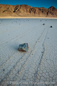 Sailing stone on the Death Valley Racetrack playa.  The sliding rocks, or sailing stones, move across the mud flats of the Racetrack Playa, leaving trails behind in the mud.  The explanation for their movement is not known with certainty, but many believe wind pushes the rocks over wet and perhaps icy mud in winter, Death Valley National Park, California