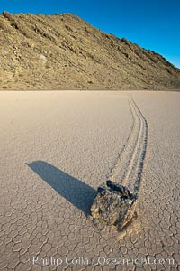 Sailing stone on the Death Valley Racetrack playa.  The sliding rocks, or sailing stones, move across the mud flats of the Racetrack Playa, leaving trails behind in the mud.  The explanation for their movement is not known with certainty, but many believe wind pushes the rocks over wet and perhaps icy mud in winter. Death Valley National Park, California, USA, natural history stock photograph, photo id 25328