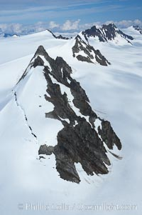 The Kenai Mountains rise above thick ice sheets and the Harding Icefield which is one of the largest icefields in Alaska and gives rise to over 30 glaciers. Kenai Range, Kenai Fjords National Park, Alaska, USA, natural history stock photograph, photo id 19016