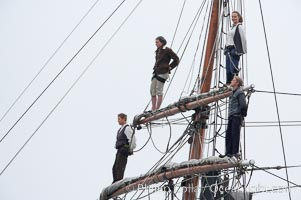Crew members stand in the rigging of the tall ship Hawaiian Chieftain, Morro Bay, California