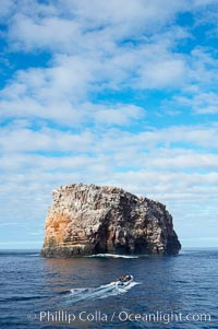 An inflatable boat full of adventurous divers heads towards Roca Redonda (round rock), a lonely island formed from volcanic forces, in the western part of the Galapagos archipelago