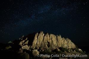 Rocks and Milky Way arching overhead, night sky and stars above, Joshua Tree National Park, California