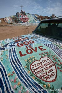 "Salvation Mountain, near the desert community of Slab City and the small town of Niland on the east side of the Salton Sea.  Built over several decades by full-time resident Leonard Knight, who lives at the site, Salvation Mountain was built from over 100,000 gallons of paint, haybales, wood and metal and was created by Mr. Knight to convey the message that ""God Loves Everyone"". California, USA, natural history stock photograph, photo id 22515"