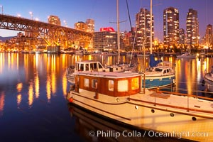 Yaletown section of Vancouver at night, including Granville Island bridge (left), viewed from Granville Island with sailboat in the foreground