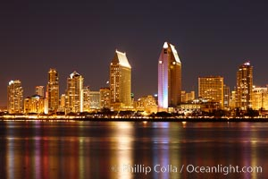 San Diego city skyline at night, showing the buildings of downtown San Diego reflected in the still waters of San Diego Harbor, viewed from Coronado Island