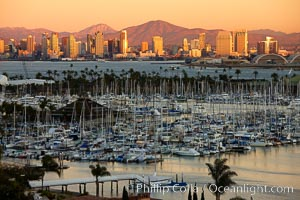 San Diego city skyline, showing the buildings of downtown San Diego rising above San Diego Harbor, viewed from Point Loma with the San Diego Yacht Club in the foreground, sunset