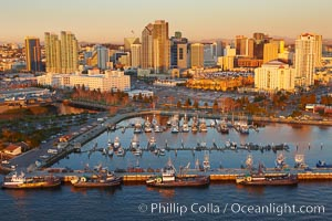 San Diego Marina District, sunset, with fishing vessels docked alongside pier, Seaport Village (right) and downtown highrise office buildings rising over San Diego Bay
