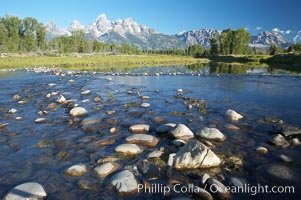 The Teton Range rises above river rocks in the Snake River at Schwabacher Landing, Grand Teton National Park, Wyoming