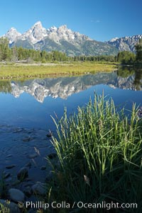 The Teton Range is reflected in the glassy waters of the Snake River at Schwabacher Landing, Grand Teton National Park, Wyoming