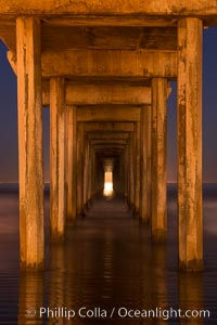 Full moon setting over the Pacific lights the inside of Scripps Pier, La Jolla, California