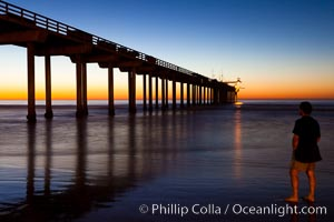 Guy watches the sunset over the SIO pier, the research pier at Scripps Institution of Oceanography SIO, La Jolla, California