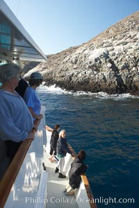 Visitors watch sea lions along the coast of Santa Barbara Island, part of the Channel Islands National Marine Sanctuary.  Santa Barbara Island lies 38 miles offshore of the coast of California, near Los Angeles