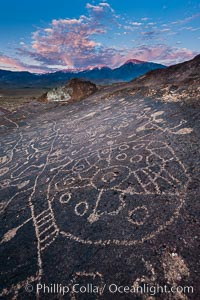 Sky Rock petroglyphs near Bishop, California, sunrise light just touching clouds and the Sierra Nevada. Hidden atop an enormous boulder in the Volcanic Tablelands lies Sky Rock, a set of petroglyphs that face the sky.  These superb examples of native American petroglyph artwork are thought to be Paiute in origin, but little is known about them