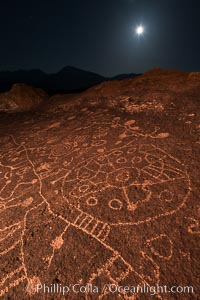 Image 28503, Sky Rock at night, light by moonlight with stars in the clear night sky above.  Sky Rock petroglyphs near Bishop, California. Hidden atop an enormous boulder in the Volcanic Tablelands lies Sky Rock, a set of petroglyphs that face the sky. These superb examples of native American petroglyph artwork are thought to be Paiute in origin, but little is known about them., Phillip Colla, all rights reserved worldwide.   Keywords: bishop:california:chalfant:chalfant petroglyphs:hidden location:indian:landscape:native american:outdoors:outside:owens valley:paiute:paiute-shoshone:petroglyph:pictograph:scene:scenery:scenic:shoshone:shoshone-paiute:sierra:sierra nevada:sky rock:southwest:volcanic tablelands:wall art:night:nightscape:astrophotography:astrophotography landscape:stars:evening:dark:dusk:sunset.