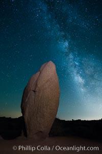 Standing stone and Milky Way, stars fill the night sky, Joshua Tree National Park, California
