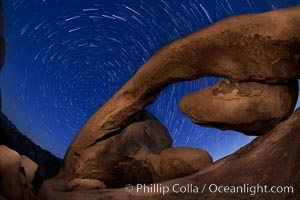 Star trails and Arch Rock. Polaris, the North Star, is at the center of the circular arc star trails as they pass above this natural stone archway in Joshua Tree National Park, Alabama Hills Recreational Area