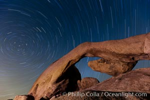 Star trails and Arch Rock.  Polaris, the North Star, is at the center of the circular arc star trails as they pass above this natural stone archway in Joshua Tree National Park. Joshua Tree National Park, California, USA, natural history stock photograph, photo id 26794