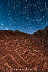 Image 28498, Star Trails over Sky Rock. Sky Rock petroglyphs near Bishop, California. Hidden atop an enormous boulder in the Volcanic Tablelands lies Sky Rock, a set of petroglyphs that face the sky. These superb examples of native American petroglyph artwork are thought to be Paiute in origin, but little is known about them., Phillip Colla, all rights reserved worldwide. Keywords: astrophotography, astrophotography landscape, bishop, california, chalfant, chalfant petroglyphs, dark, dusk, evening, hidden location, indian, landscape, native american, night, nightscape, outdoors, outside, owens valley, paiute, paiute-shoshone, petroglyph, pictograph, scene, scenery, scenic, shoshone, shoshone-paiute, sierra, sierra nevada, sky rock, southwest, star trail, stars, sunset, volcanic tablelands, wall art.