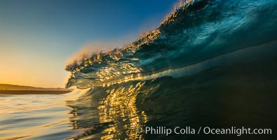 Sunrise glints yellow on breaking wave, dawn surf, The Wedge, Newport Beach, California