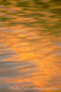 Orange aspen trees are reflected in the smooth calm water of North Lake, Bishop Creek Canyon, Sierra Nevada Mountains