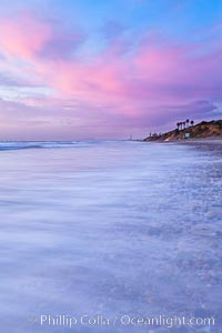 Sunset and incoming surf, gorgeous colors in the sky and on the ocean at dusk, the incoming waves are blurred in this long exposure, Carlsbad, California