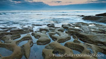 Waves wash over sandstone reef, clouds and sky, La Jolla, California