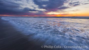 Surf and sky at sunset, waves crash upon the sand at dusk, Carlsbad, California