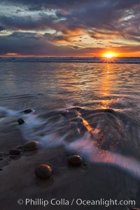 Surf and sky at sunset, waves crash upon the sand at dusk, Carlsbad, California