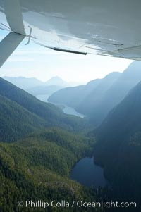 Shelter Inlet of Clayoquot Sound (distance) and small lake (foreground), amid the coastal mountains of western Vancouver Island, aerial photo, Megin Lake