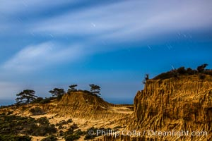 Torrey Pines State Reserve at Night, stars and clouds fill the night sky, the Pacific Ocean in the distance, San Diego, California
