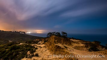 Torrey Pines State Reserve at Night, stars and clouds fill the night sky with the lights of La Jolla visible in the distance. San Diego, California, USA, natural history stock photograph, photo id 28406