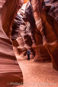 A hiker admiring the striated walls and dramatic light within Antelope Canyon, a deep narrow slot canyon formed by water and wind erosion, Navajo Tribal Lands, Page, Arizona