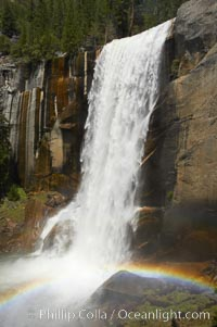 Vernal Falls at peak flow in late spring, with a rainbow appearing in the spray of the falls, viewed from the Mist Trail, Yosemite National Park, California