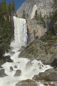 Vernal Falls and the Merced River, at peak flow in late spring.  Hikers ascending the Mist Trail visible at right.  Vernal Falls drops 317 through a joint in the narrow Little Yosemite Valley, Yosemite National Park, California