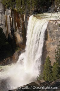Vernal Falls at peak flow in late spring.  Hikers are visible at the precipice of the waterfall.  Viewed from the John Muir Trail.  Vernal Falls drops 317 through a joint in the narrow Little Yosemite Valley, Yosemite National Park, California