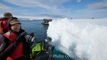 Visitors enjoy a look at penguins on an iceberg from an inflatable boat, Paulet Island