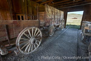 Wagon and interior of County Barn, Brown House and Moyle House in distance. Bodie State Historical Park, California, USA, natural history stock photograph, photo id 23142